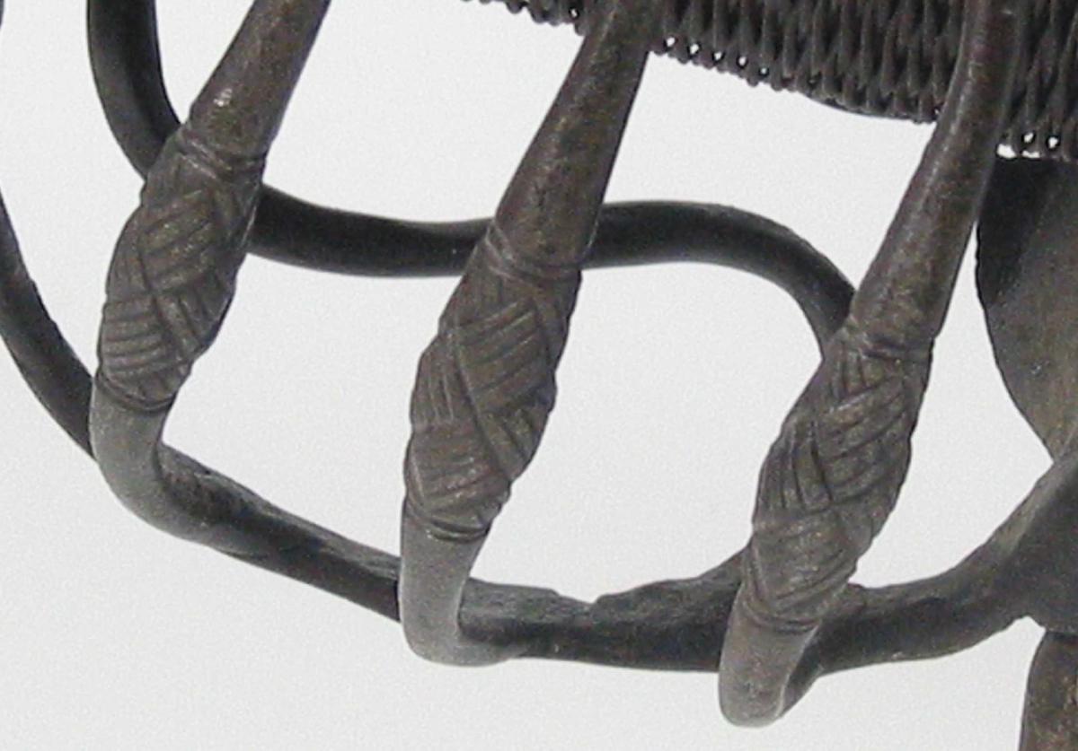 Pyramideformet knapp med kryssfilt dekor. Asymmetrisk feste med tre sidebøyler på utsiden med dekorerte fortykninger på midten. Innsiden har to sidebøyler og  tommelbøyle. Nyreformet parérplate . Svalt nedbøyde parérstenger med rundt tverrsnitt og kryssfilte fortykninger på endene.Fremre parérstang er brukket og fornyet. Tregrep med jernvikling. Enegget krum klinge med tre smedstempller på venstre side. Klingen har bred hulslipning og gjeddenebb.