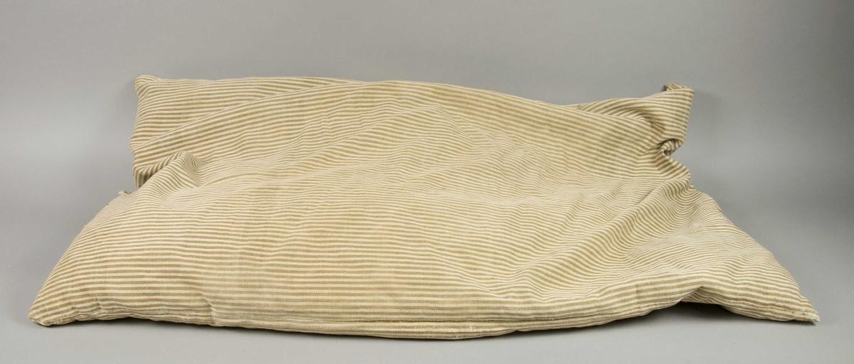 Pute med vevd trekk av stripete bomull, fylt med treflis.