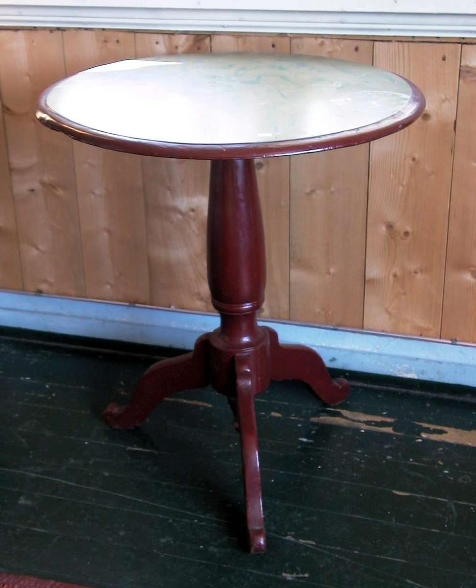 Rundt bord på søyle med tre ben. Foten er rødmalt. Bordplaten er malt i grønnblå marmorering. Kanten er rød.