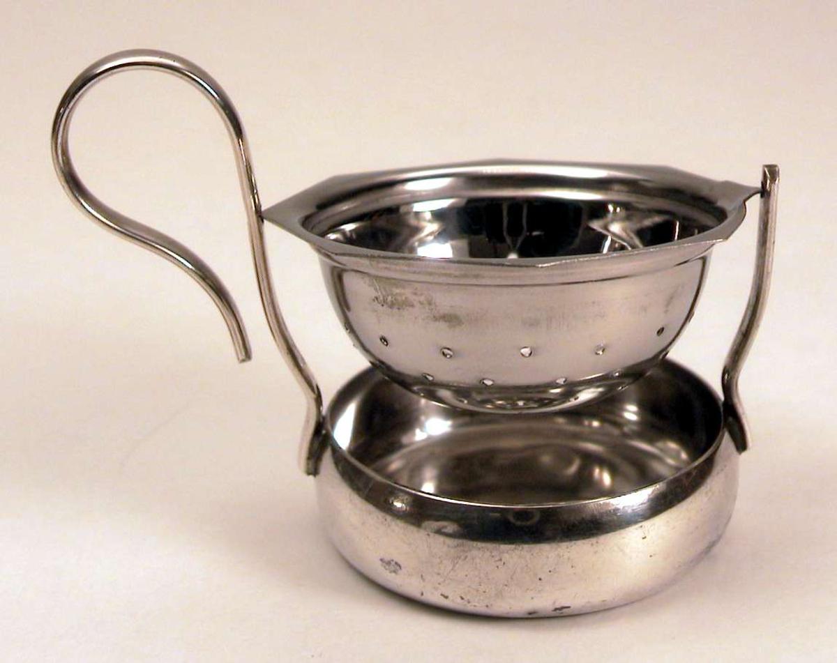 Tesil som består av holder med håndtak og svingbar sil. Holderen er i sølvplett.