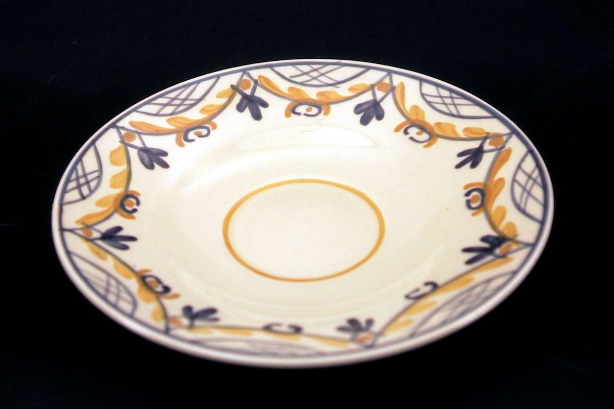 Skål i lys gul fajanse med håndmalt dekor i lilla og oker.