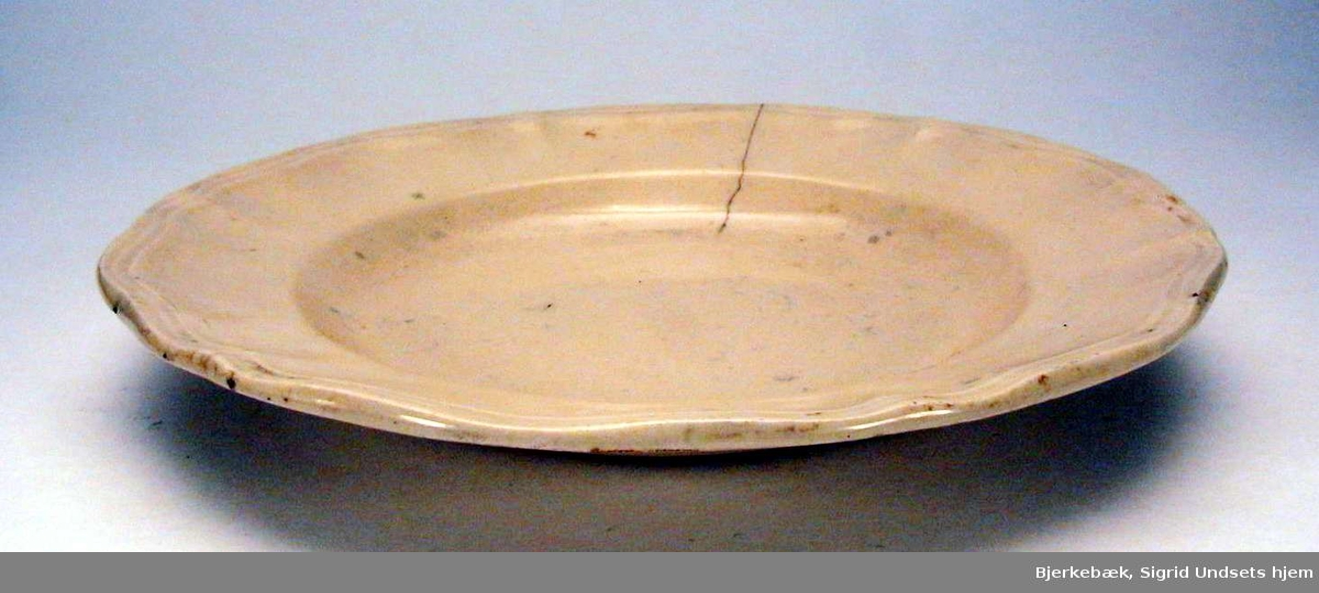 Elfenbensfarget dyp tallerken. Den har rifler langs kanten. Det er sprekk i tallerkenen. Det er et skår i kanten.