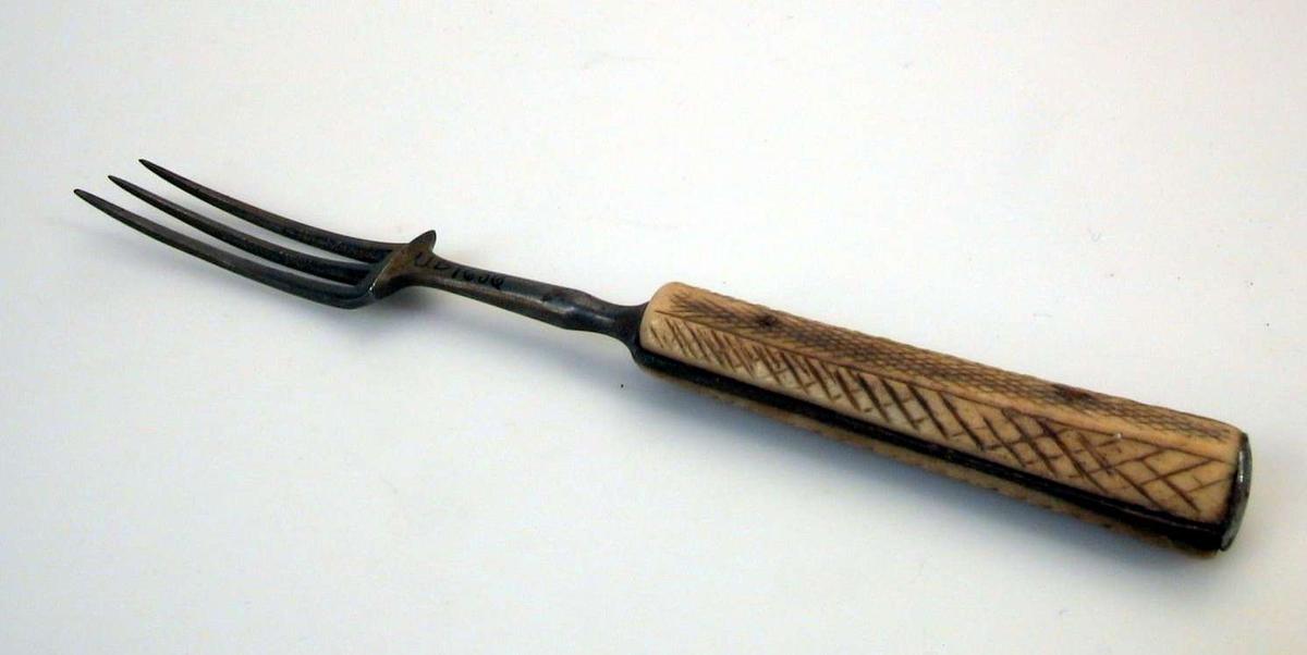 Gaffel med tinder av jern, skaft av ben. Skaftet har et enkelt, stilisert mønster.