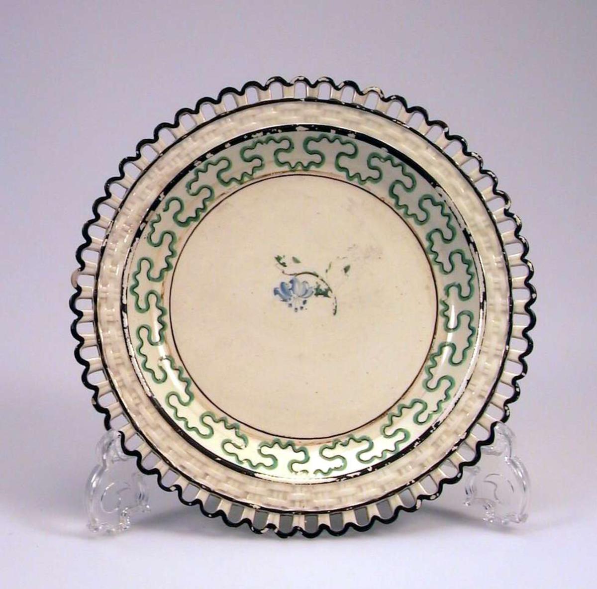 Tallerken i keramikk med kremfarget glasur og med dekor i brunt, grønt og blått. Den har 'hullfallskant'.