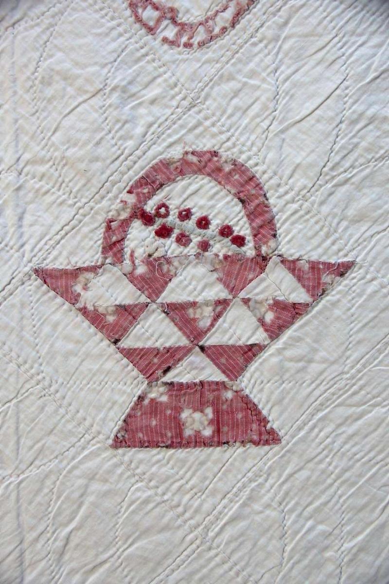 Sengeteppe i rosa/rødt på hvit bunn. Bomull. Applikasjoner med kurvmotiver med frukt/blomster i noen varierte farger. Vattering av flanell, fór av lerret.
