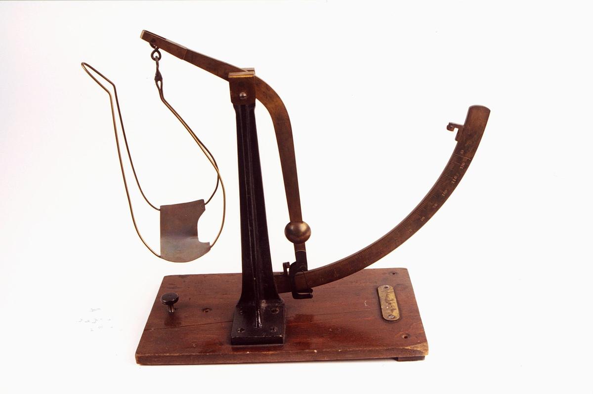 Pendel/skålvekt i metall montert på trefot.