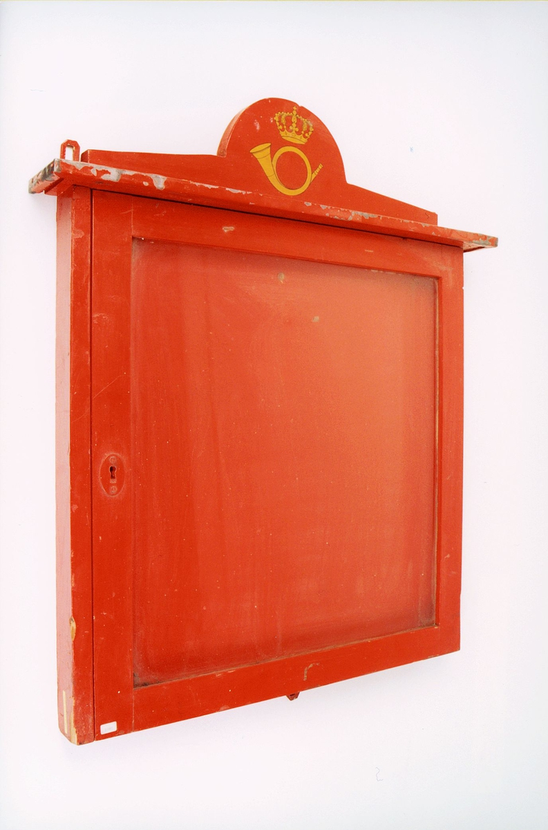 Rød plakatramme i treverk med glass. Posthornemblem på toppen. Låsbar.