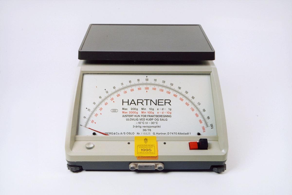 Hartner Modell B2000, brevvekt, brev- og småpakkevekt.. Postlogo i gult på baksiden. Vekt med to veieskalaer. Veieområde: 10 - 2000 g. Max 200 g - min 10 g. Max 2000 g - min 100 g. FK 315.14.00 ex 1 - nr. 11552