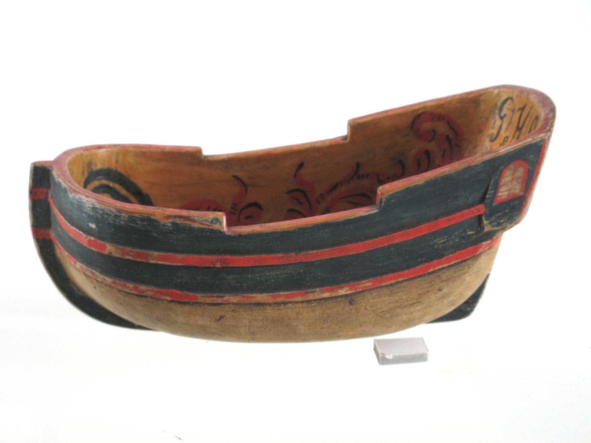 Innvendig  dekorert med ranker i rødt, grønt og sort samt et  anker og et hjerte i rødt og sort, alt på gul bunn.