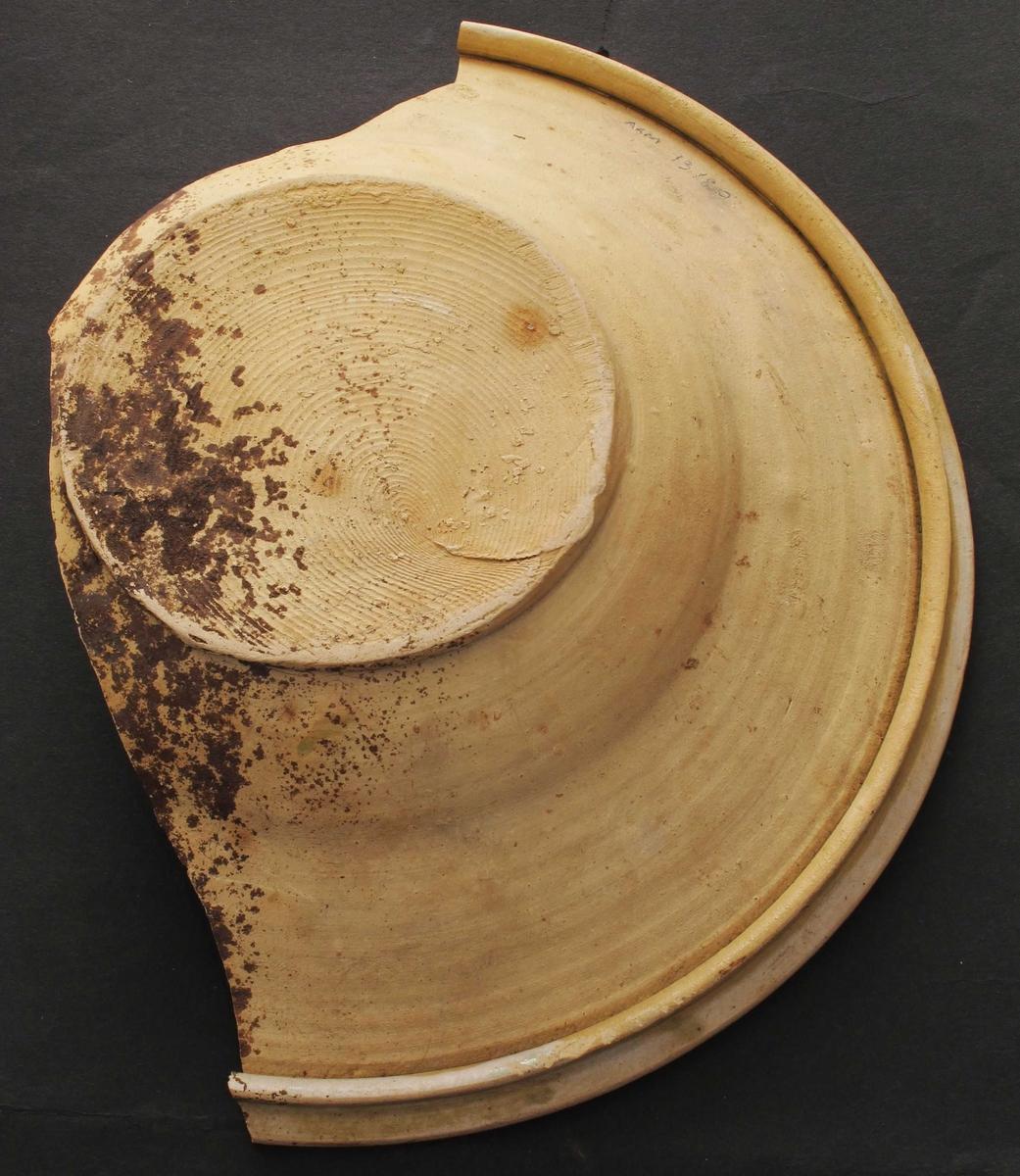 """Fat. Leirtøy, grågult gods, rillet bunnavskjæring.  Utvendig uglasert, innvendig hvitgrå begitning med """"slipdekor"""" (rankespiraler) i brunrødt, mørkebrunt.  Markert bunnflate, utvendig brem med hulkil.  Innvendig høy, skrå brem, bred, dekorert med en rankespiral, regelmessig.  I speilet samme dekor, seks spiraler omkring en spiral i midten.  I overgang til brem, og landskanten ytterst brunrøde ringer.  Tilstand:  speilet helt, men halve bremmen borte."""