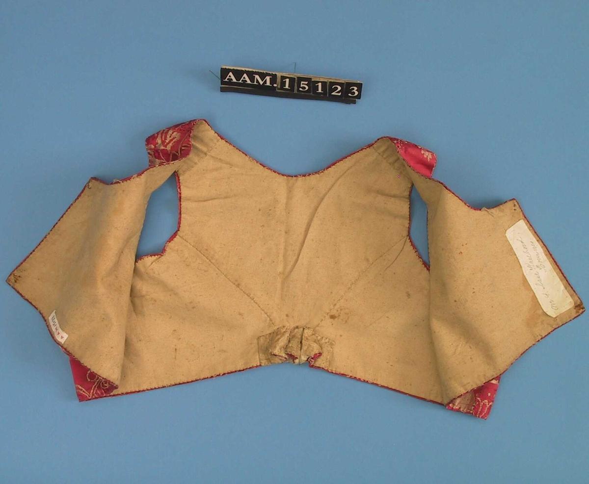 Upplut,  av  silkedamask,  karmosinrød.   Finvevd lerret, naturfarget i foret.   Håndsøm, grå tråd.    Helskårne forstykker med nedringning, har hatt to kraftige hekter,  som giver har sprettet av. Ryggen har midtsøm og to bærestykker  som går i bue ned mot midten, hvor det er vel 2em. høye folder.  Det venstre sidestykke har en kile ved ermeutringningen.  Tilstand: noe mørkflekket under armene. På det ene forstykke en  lys skjold med mørke kanter På foret nederst merker etter hekter rust