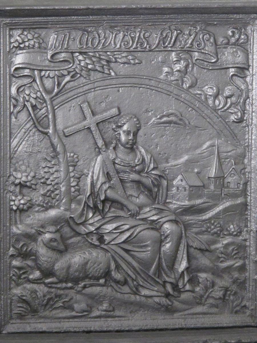 """Langsiden med """"Troen"""" som sittende kvinnefigur i landskap, med kors i høyre hånd, lam liggende i forgrunnen til venstre.  I bakgrunnen til høyre by med byport og kirke, regnbue på himmelen og banderoll med """"in adveris fortis"""" - styrke i motgang.  Faste sideskinner med laurbærblad og bær.  Kortside med putto med overflødihetshorn stående i nedre felt, samt ANNO 1730.  I øvre felt oppstilt på postament, flankert av palme og laurbærtre, kvinnebyste (""""troen"""") som krones av Guds arm ned fra skyen oppe til venstre.  På postamentet innskrift """"Operis victoria finale"""" - verket krones med seier til slutt."""