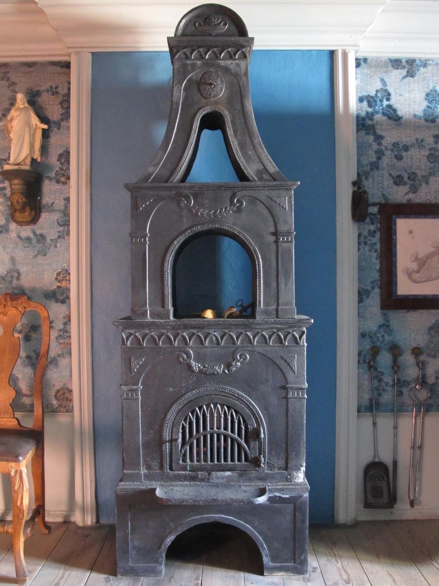 Kentaur - men denne er kun avbildet på ovnens bakside, der gitterdøra er på forsiden.  Pilastre/ volutter/ guirlander./ buefrise.