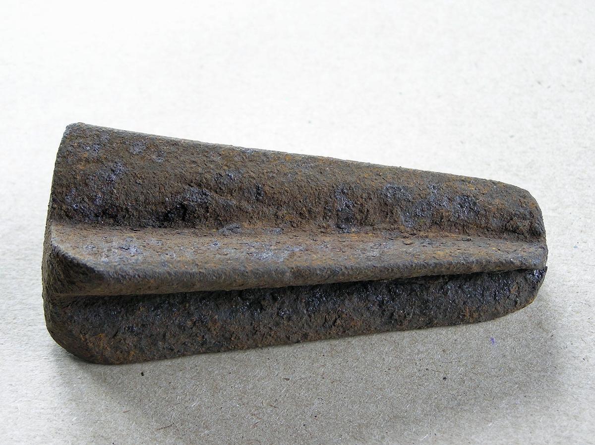 Smidd jernstykke til bruk ved smiing av merkeøks. Merket ble formet rundt stempelet. Uten håndtak - antagelig holdt med tang. Noe rust.