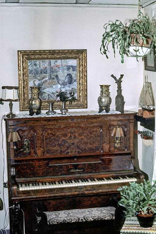 Albrethsen Fagfor. hus. Leilighet, stue, piano, bilde på vegg.