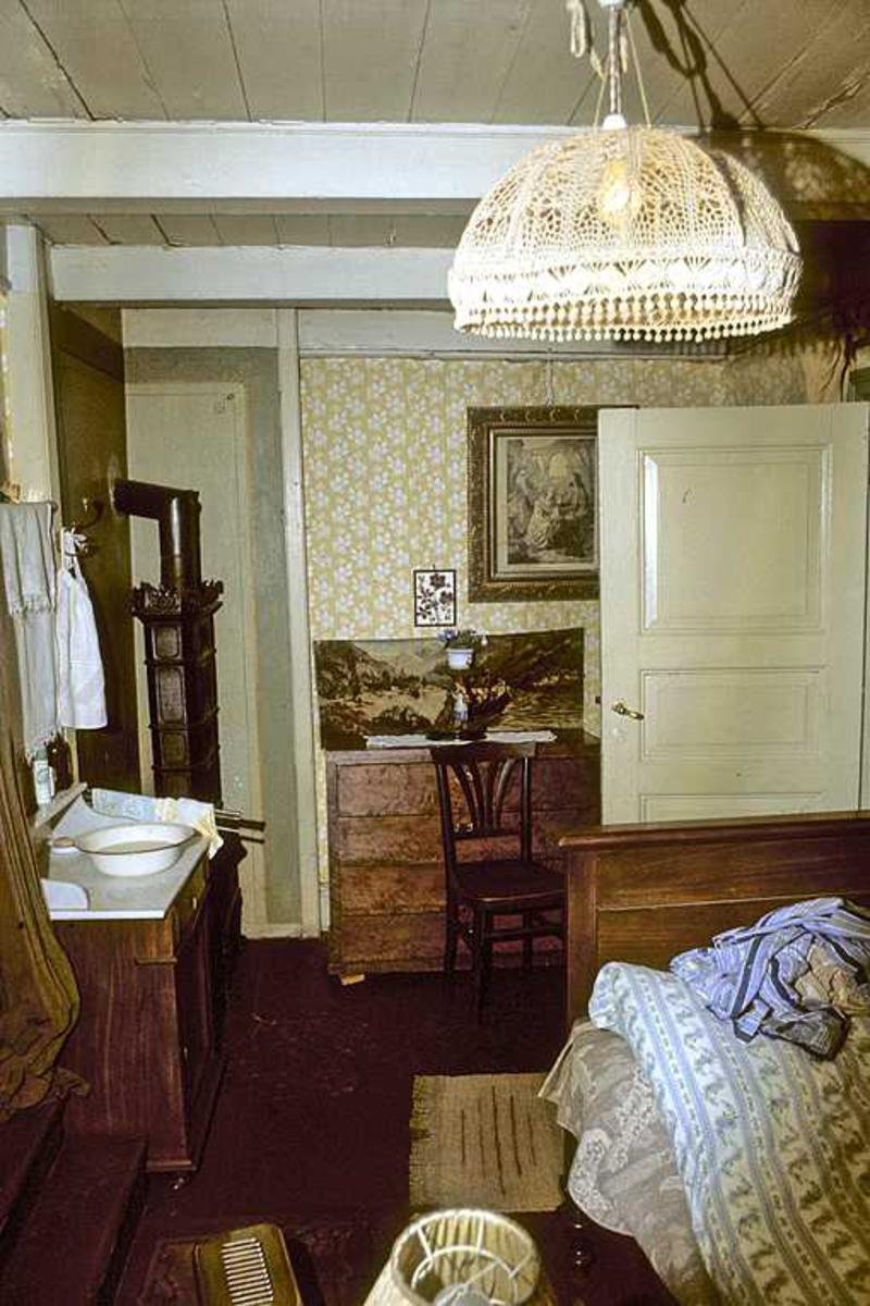 Interiør fra Tyholmen. Elektrisk taklampe, jernovn, kommode, bilder på veggene.