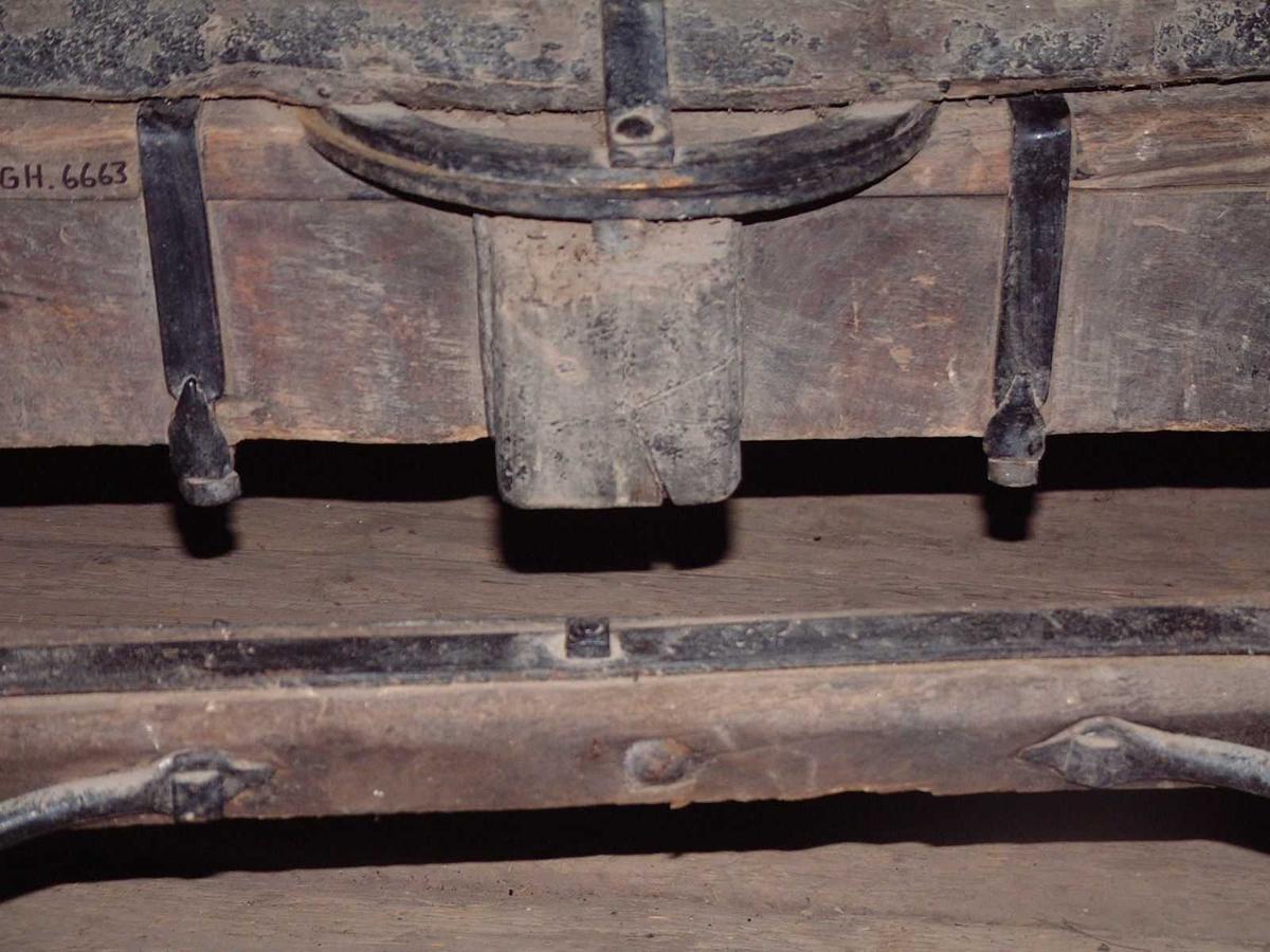 Svingflak med doble svingringer. Kraftig treaksel med rektangulært tverrsnitt. Kraftig jernbeslag på overkant av svingflak. Faste jernkeiper; den venstre mangler. Jernbeslåtte trehjul med svak styrt. 6 fell, 12 eiker. Originalt drag med jernbeslag på innsiden mot hull til orering.
