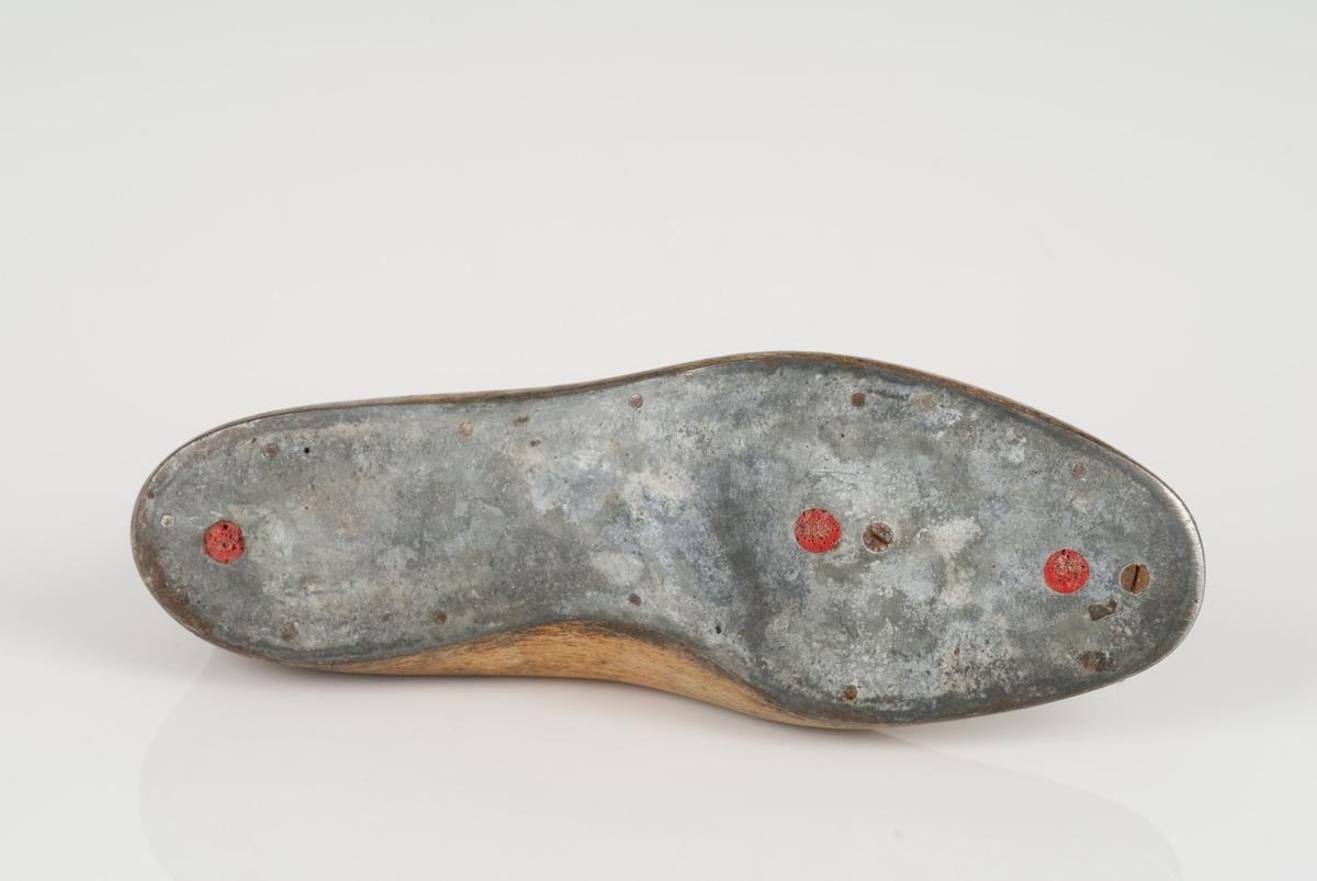 En tremodell i to deler; lest og opplest/overlest (kile). Høyrefot i skostørrelse 42. Såle av metall. Lestekam av skinn.