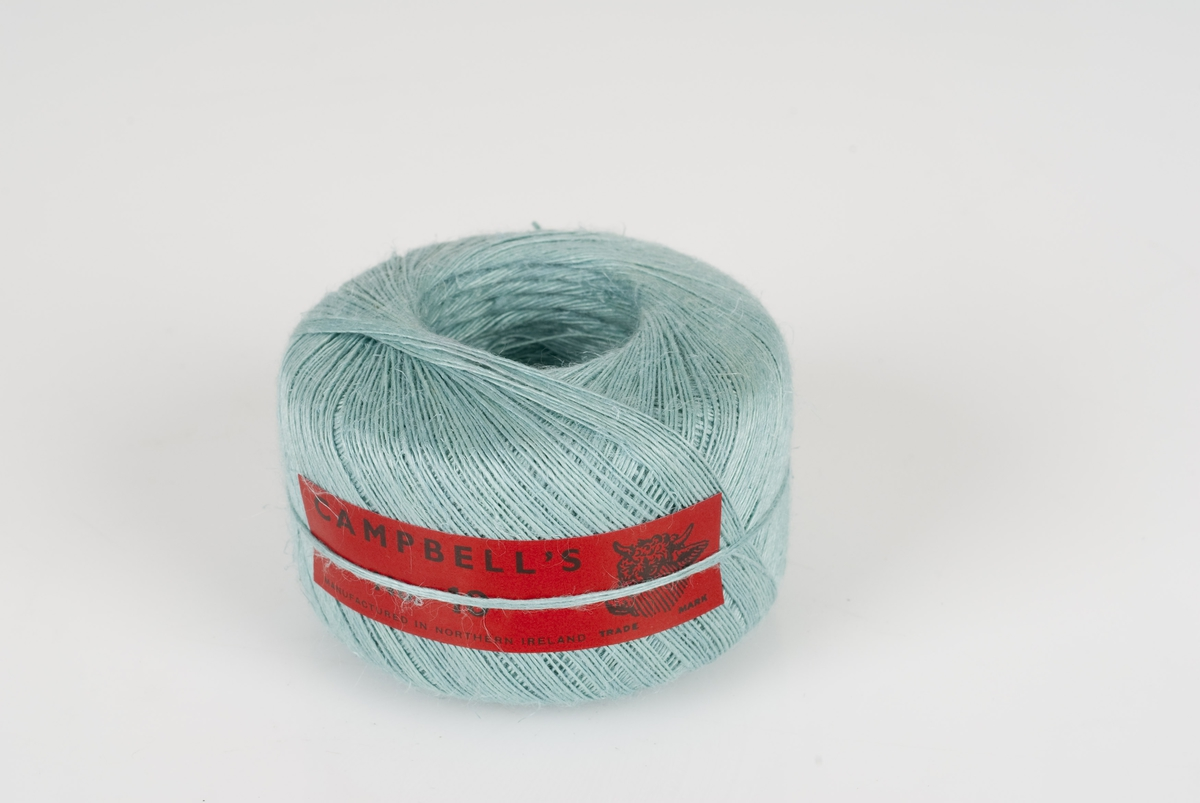 Tynn lysblå lintråd i rull. Påklistret rød merkelapp med påført tekst.