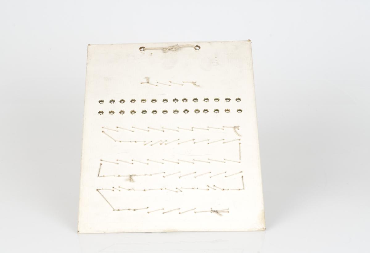 En prøveplate med forskjellige typer maljer påfestet på platen. Maljene er av jern og messing Antall melajer på platen er 89. Påført tekst på platen.
