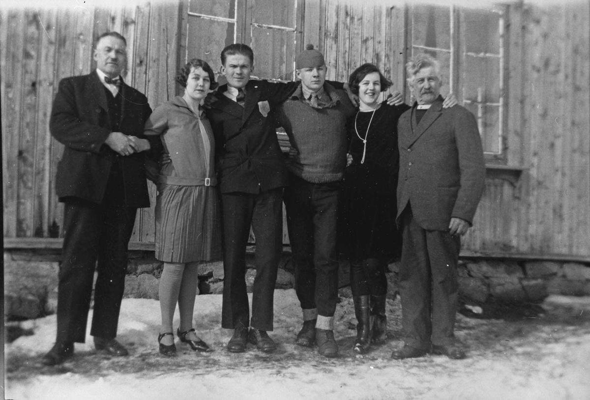 Gruppebilde. Fire menn og to kvinner oppstilt utenfor et hus.