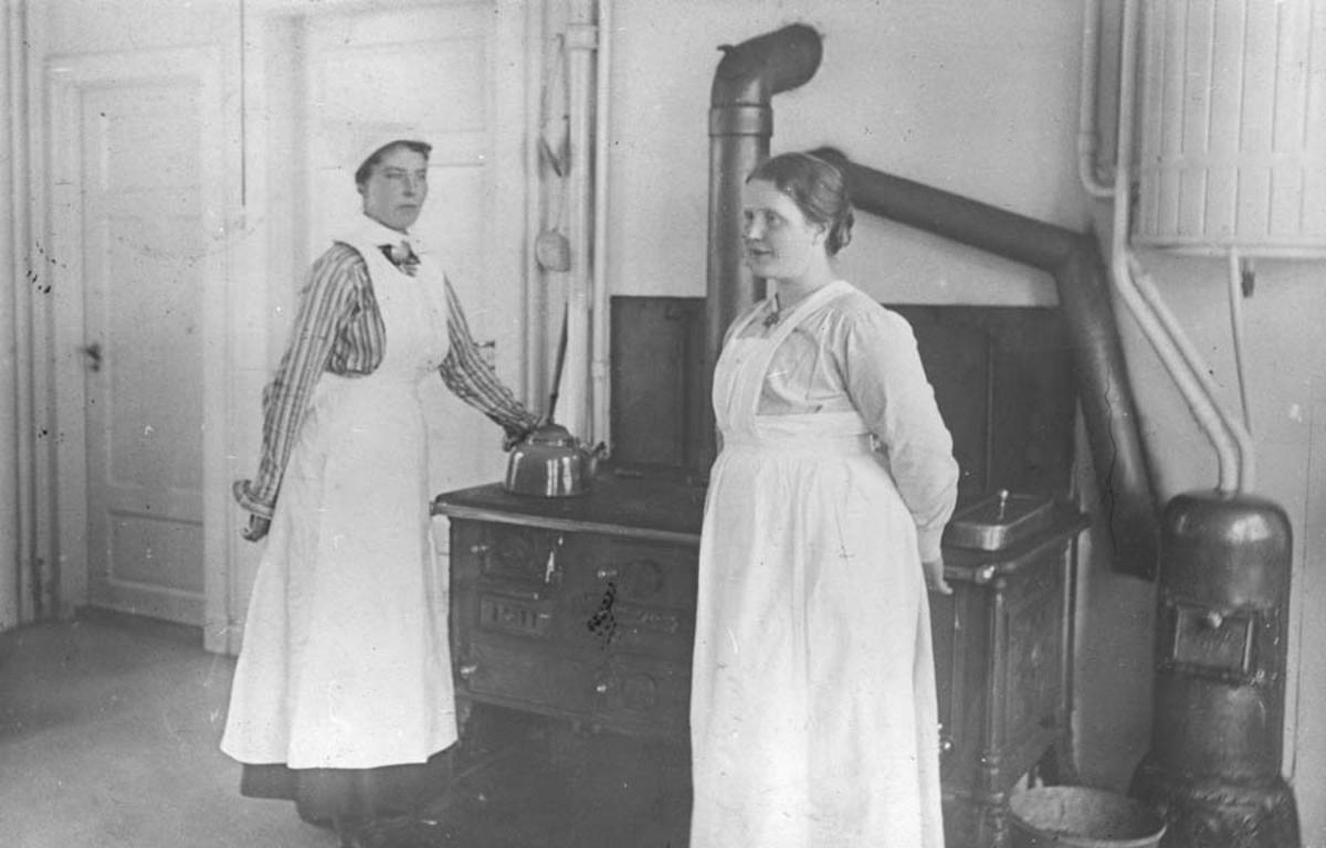 Follo tuberkulosehjem. To ansatte ved komfyren på kjøkkenet.