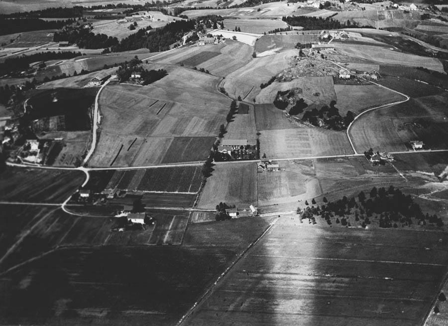 Flyfoto av gårder, jorder og skogholt. Vi ser ut over Tuenveien