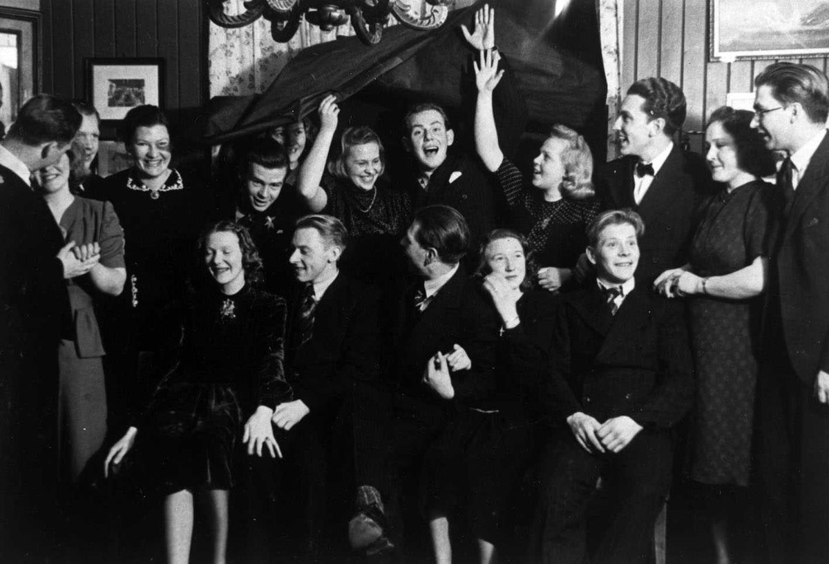 """Fest med """"nedfall"""" på Skogvold 1943. (Det er blendingsgardinen som faller ned) Festkledd forsamling oppstilt for fotografering. De i bakre rekke løfter gardinen over hodet."""