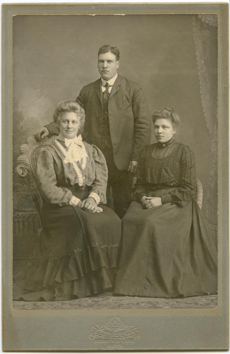 Gruppebilde. En mann og to damer. Bildet er tatt hos fotograf