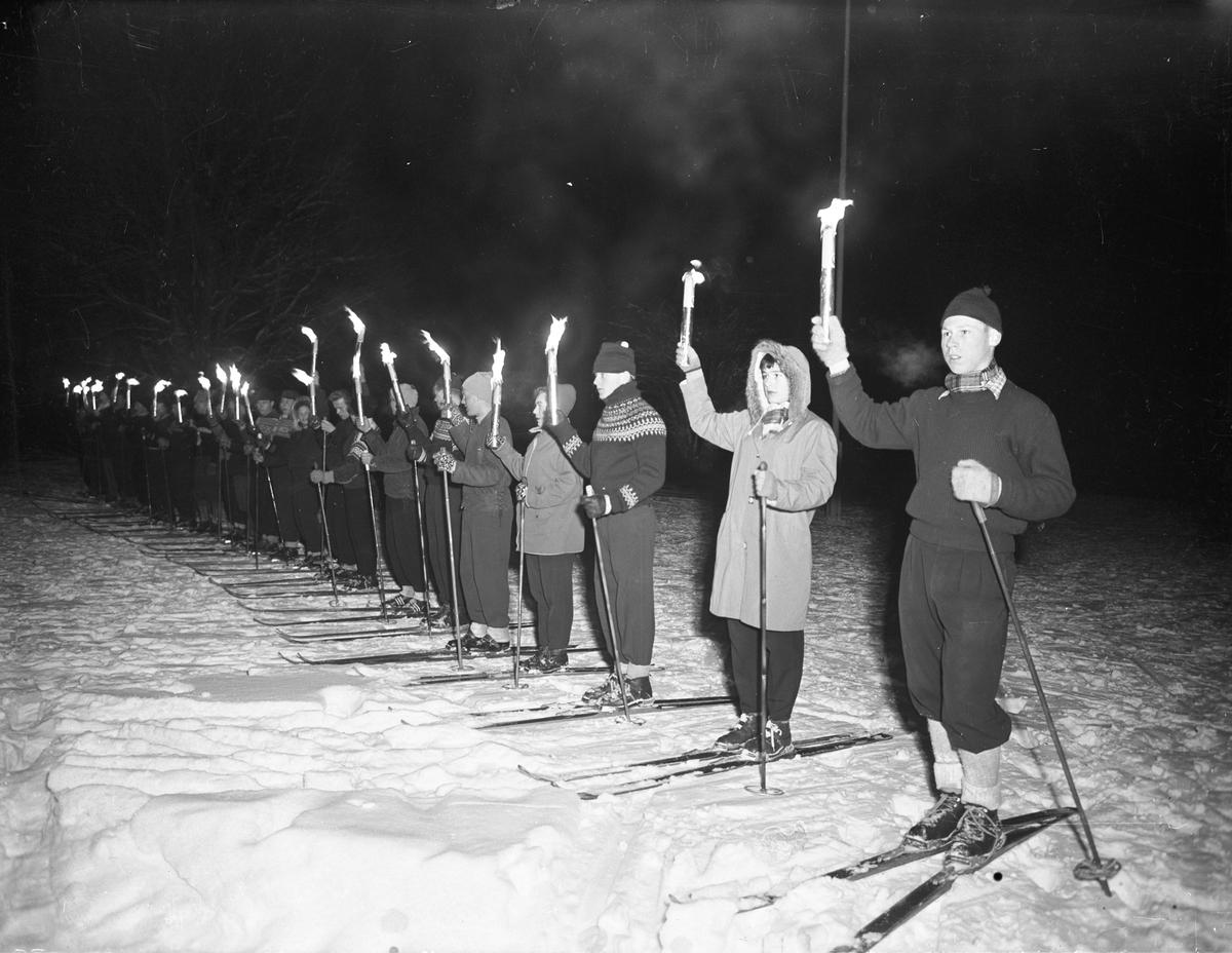 Skiløpere med fakler.