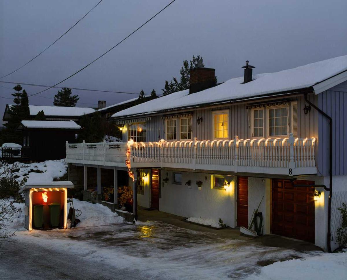 Julebelysning  Lysende snømenn og lysslange snodd rundt rekkverk på veranda. Hvit lysslange og lysende engel på søppelhus ved enebolig