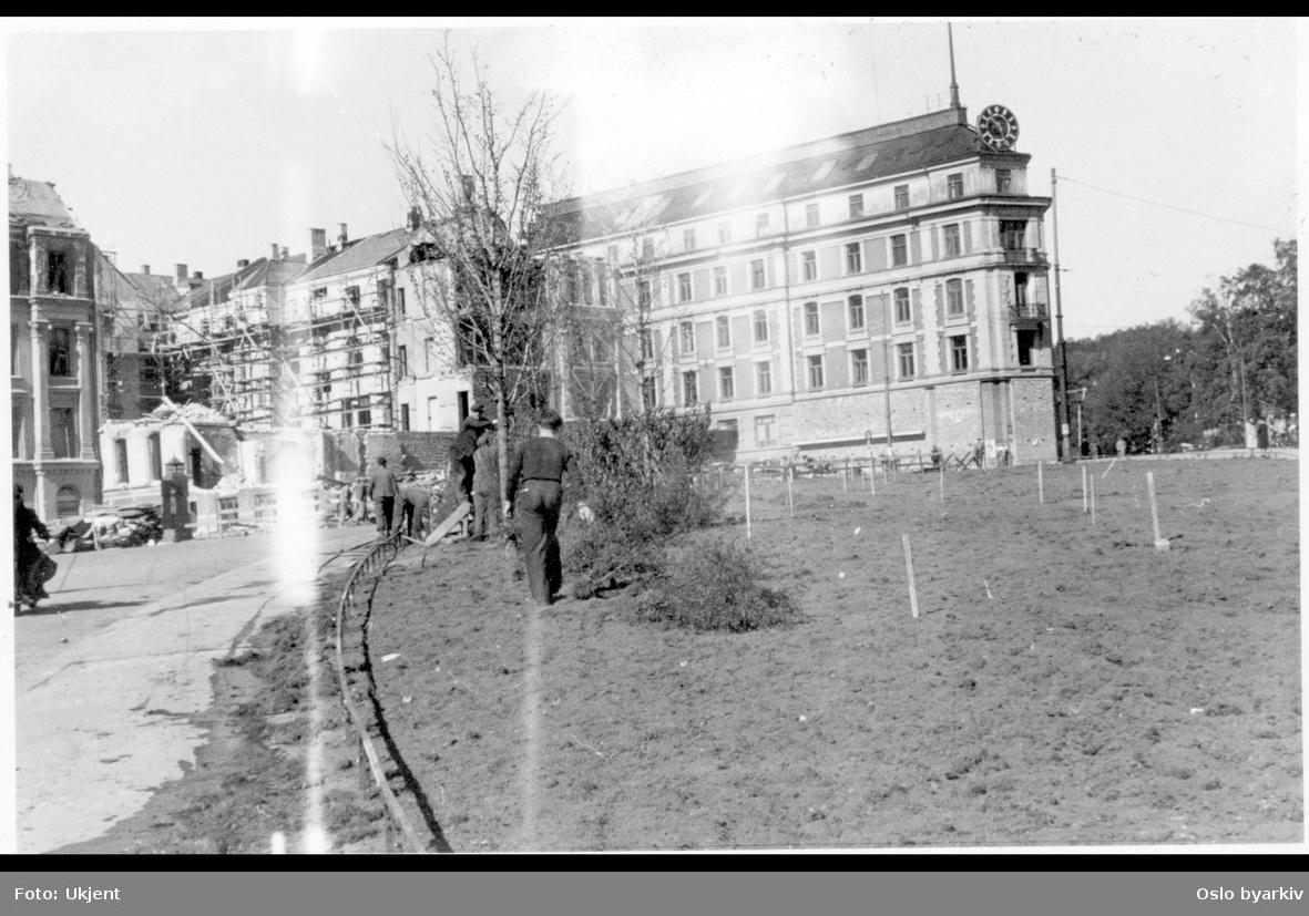 Triangelplassen (i dag 7. juni plass) opparbeidet med langsmalt grøntanlegg. Arbeidere i gang med beplantning av busker og trær. I bakgrunnen til venstre ruinene av Drammensveien 2 (etter mislykket engelsk bombing mot Victoria terrasse nyttårsaften 1944). Bebyggelse i Kronprinsens gate og Glitnegården i Henrik Ibsens gate (tidligere Drammensveien) 4 med uret på taket.