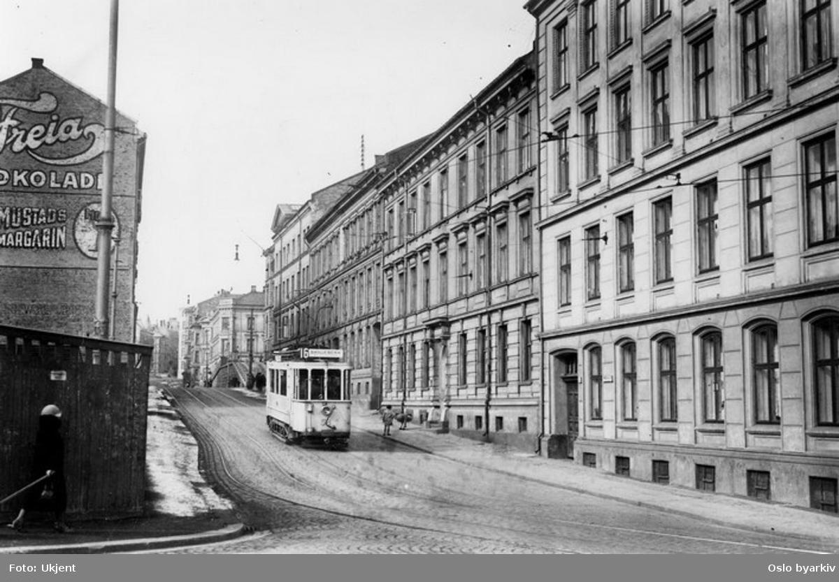Oslo Sporveier. Trikk motorvogn 58 type SS lang (fra 1912, modernisert 1921) linje 16, Skillebekk-Vålerenga via Vest- og Østbanen, i Cort Adelers gate. To barn leker på fortau. Gavlvegg-reklame for Freia sjokolade og Mustads margarin.