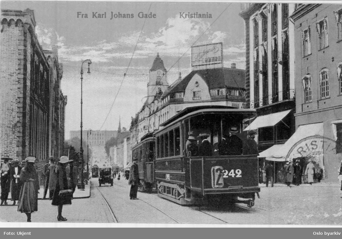 """Karl Johans gate fra Egertorget mot Slottet. Trikk med tilhenger på linje 12 til Majorstuen, motgående bil og trikk. Stortinget, Tostrupgården. Spaserende. Postkort.Bildet er enten tatt sommeren 1916 og i så fall er skiltet bak på vogn 242 feil, men kan forklares med at konduktøren har glemt å sette det riktig. Det burde ha stått """"9"""", men 9 og 12 var kombinert. Eller det er tatt i 1919 før vogna 242 fikk nytt nummer 297. Linje 12 kom tilbake til Karl Johans gate seint i 1918, men hers er det jo sommerlig ut."""