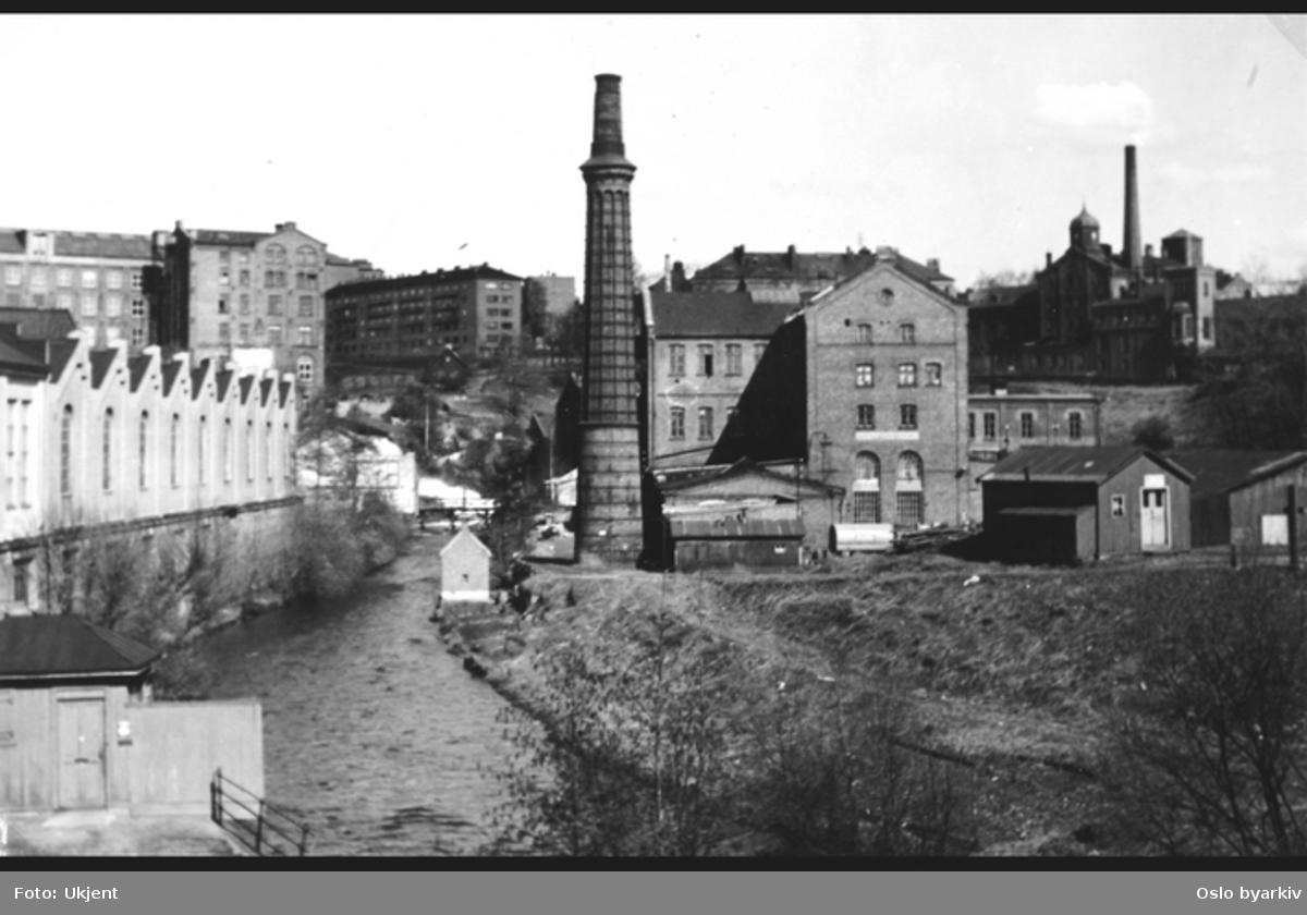 Akerselva mot Beyerbrua. Tatt fra Sannerbrua. Renovasjonsstasjon for Aker. Tidligere Vaaghalsens Barkestampe, Vaaghalsens Maltmølle, senere Vøiens Bomuldsspinderi/Nedre Vøien Spinderi. I bakgrunnen, øverst ved fossen Våghalsen (nederste av Vøyenfallene), skimtes Hønse-Louvisas hus.