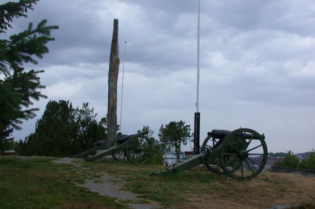 Ca 11 m høy bauta med bronseplate flankert av kanoner, kanonkuler og flaggstenger.