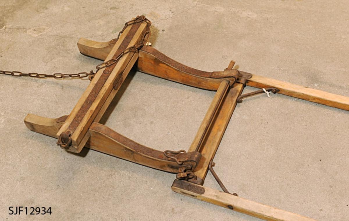 """Gjenstanden er en miniatyrutgave av en ordinær tømmerrustning utført i målestokken 1:4. En ordinær tømmerrustning som trekkes av hest ville altså være 4 ganger større. Tømmerrustningen er konstruert som en leke for barn. Den trekkes av mennesker. Gjenstanden består av tre deler, drag, bukk og geit som sammen utgjør barnesleden, tømmerrustningen.  Draget (dragarmene), """"skjekene"""", er utformet slik at et barn kan få godt grep om dem når de skal dra rustningen etter seg. Trekkstengene har en krumning som til forveksling ligner en trillebårs håndtak. Draget er festet til en kjelke, bukk. På yttersiden av bukkemeiene er det et jernbeslag med en ring. Draget har tilsvarende ring. Ringene tres i hverandre og holdes festet sammen med en trekile (en slags selepinne). Draget kan dermed lett festes til og løsnes fra bukken. Bukken har en fast bank som er nedfelt i bukkens meier, dyne. Oppå den faste banken er det festet en svingbank som er jernbeslått i hele bredden. I hver ende på svingbanken er det en smidd jernring. Til den ene jernringen er det festet en kjetting. Kjettingen brukes til å stramme lasset fast til bukken. Stramminga foretas med benningsbjønn.  Meiene på bukken har jernskoning. Skoningen er bøyd over meiespissene og cirka 46 cm bakover på meienes overside. På bukkens faste banke er det en jernkrok som geita, den bakre kjelken, festes til. En jernlenke, trosse, er festet til to jernringer, hengsler, i geitmeiens jernskoning. Denne jernlenken, kjettingen, festes til kroken på bukkens faste bank. Geita har en fast bank som også har jernbeslag i hele bredden og en jernring i hver ende. Gjennom hver jernring er det tredd en kjetting. Disse kjettingene brukes til å stramme lasset. Det sitter en benningsbjønn festet til jernlenkene. Opprinnelig hørte det to benningsbjørner (bjønner) til sleden, men det er kun denne ene igjen. Lenger fram på meiene er det festet en tverrstokk. Geita har vegmeier som går fra den faste banken via tverrstokken fram til meiespissene. Geitm"""