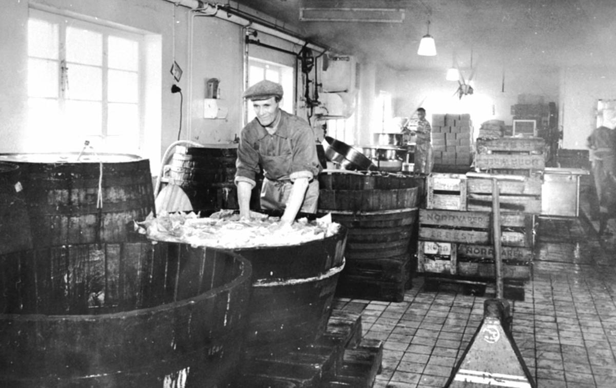 Interiør. A/S Oplandske Konservesfabrikk, Stabburet, Nora, Brumunddal. Harals Waldemarsen skyller plastposer etter sveising, ved store trebutter.