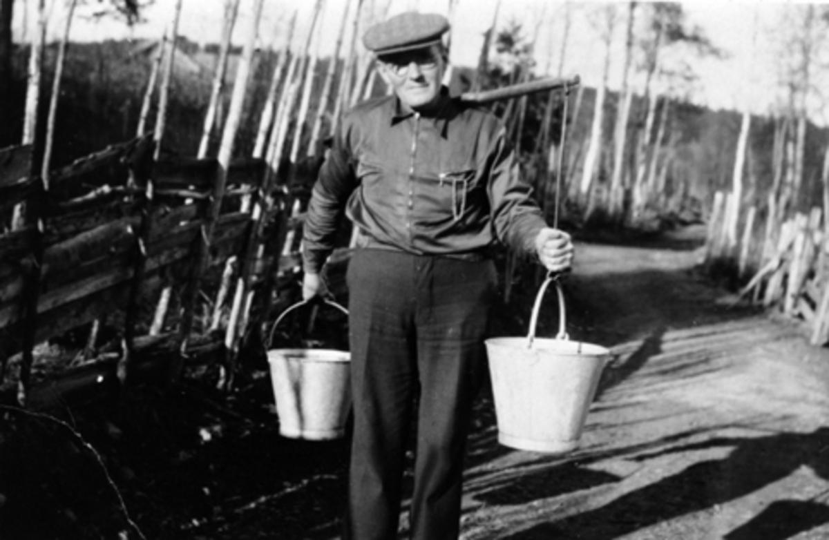 INGMAR ØSTERAAS BÆRER VANN I SINKBØTTER, BÆRESELE, KASTBAKKEN, MOELV. 1943.