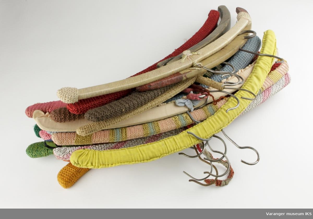 Samling av kleshengere, 20 stk. Av disse er 18 kledd i en eller annen form for tekstil, enten strikk, stoff, tråder eller en kombinasjon av disse teknikkene.