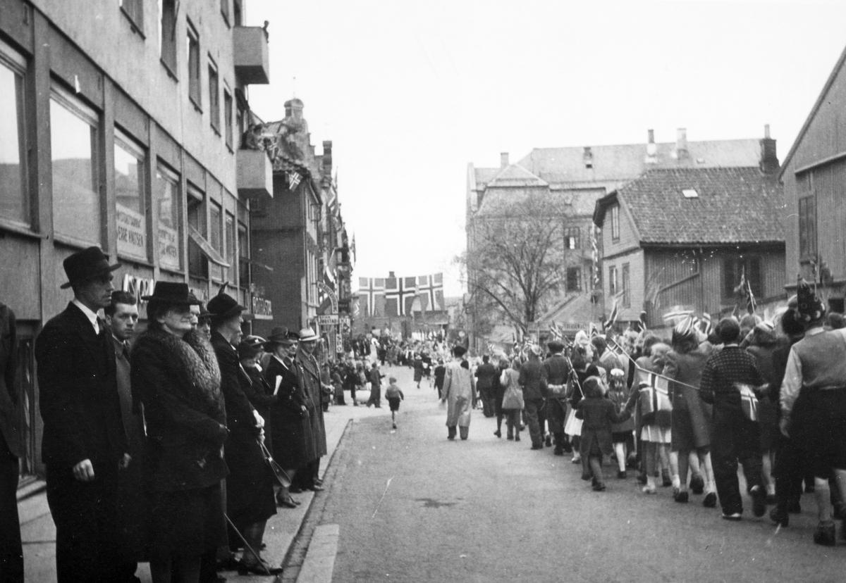 Skoletoget 17. mai 1945 passerer gjennom Torggata utenfor Astoria hotell.  Fredsdagene etter 2. verdenskrig.