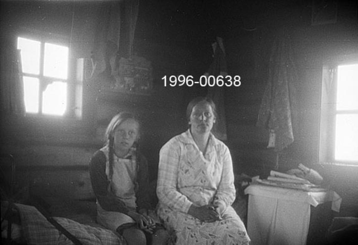 """Fra Byringen skogbrannvaktstasjon øst for Storsjøen i Ytre Rendalen.  Stasjonen ligger 1031 meter over havet, og ble bygd av skogeier S. Sjølie i 1904.  Fotografiet viser interiøret i brannvaktstua etter første ombygging, antakelig omkring 1930. To personer personer, ei ungjente og ei voksen kvinne, sitter på en brisk eller ei seng ved hytteveggen.  Dette er skogbrannvakt Aslaug Kvernbuen (1895-1977) og hennes datter Jorunn (1919-2009).  I bakgrunnen skimtes tømmervegger med opphengte klesplagg og to smårutete vinduer.  Opptaket er dessverre noe uskarpt.   Møtet med Jorunn Kvernbuen og brannvaktstasjonen på Byringen inspirerte Berhnard Stokke (1896-1979) til å skrive ungdomsboka """"Den ensomme vaktpost"""", jfr Paul Tage Halbergs kommentar i rubrikken """"Andre opplysninger""""."""