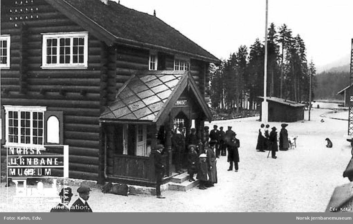 Tinnoset stasjon med reisende foran stasjonsbygningen