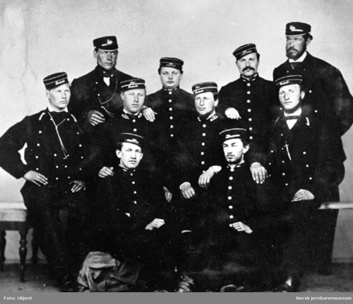 Gruppebilde av ti uniformerte jernbaneansatte fra Størenbanen med forskjellige uniformer og luer