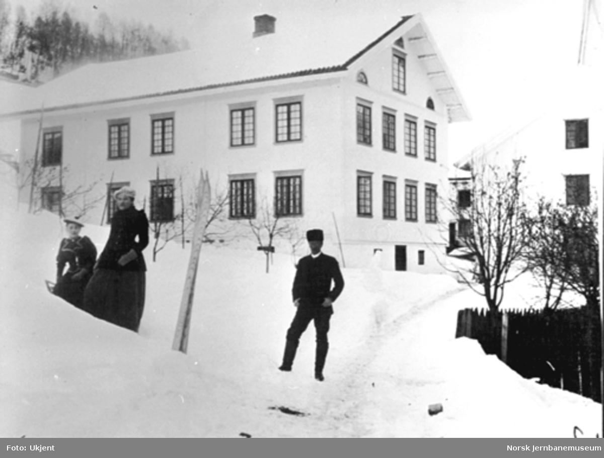 Vinterbilde av hovedbygningen på Berg gård i Ringsaker. To jenter og en mann poserer i forgrunnen