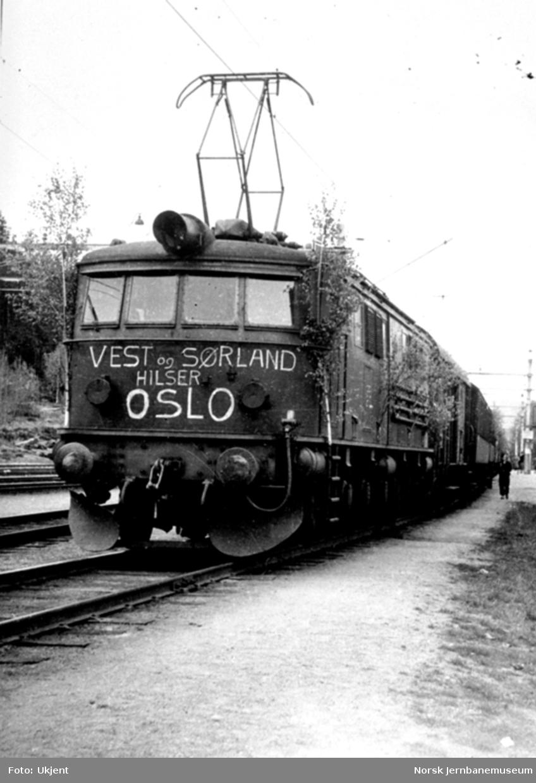 """Elektrisk lokomotiv i tog 706 pyntet løv og påskrevet """"Vest og Sørland hilser Oslo"""""""