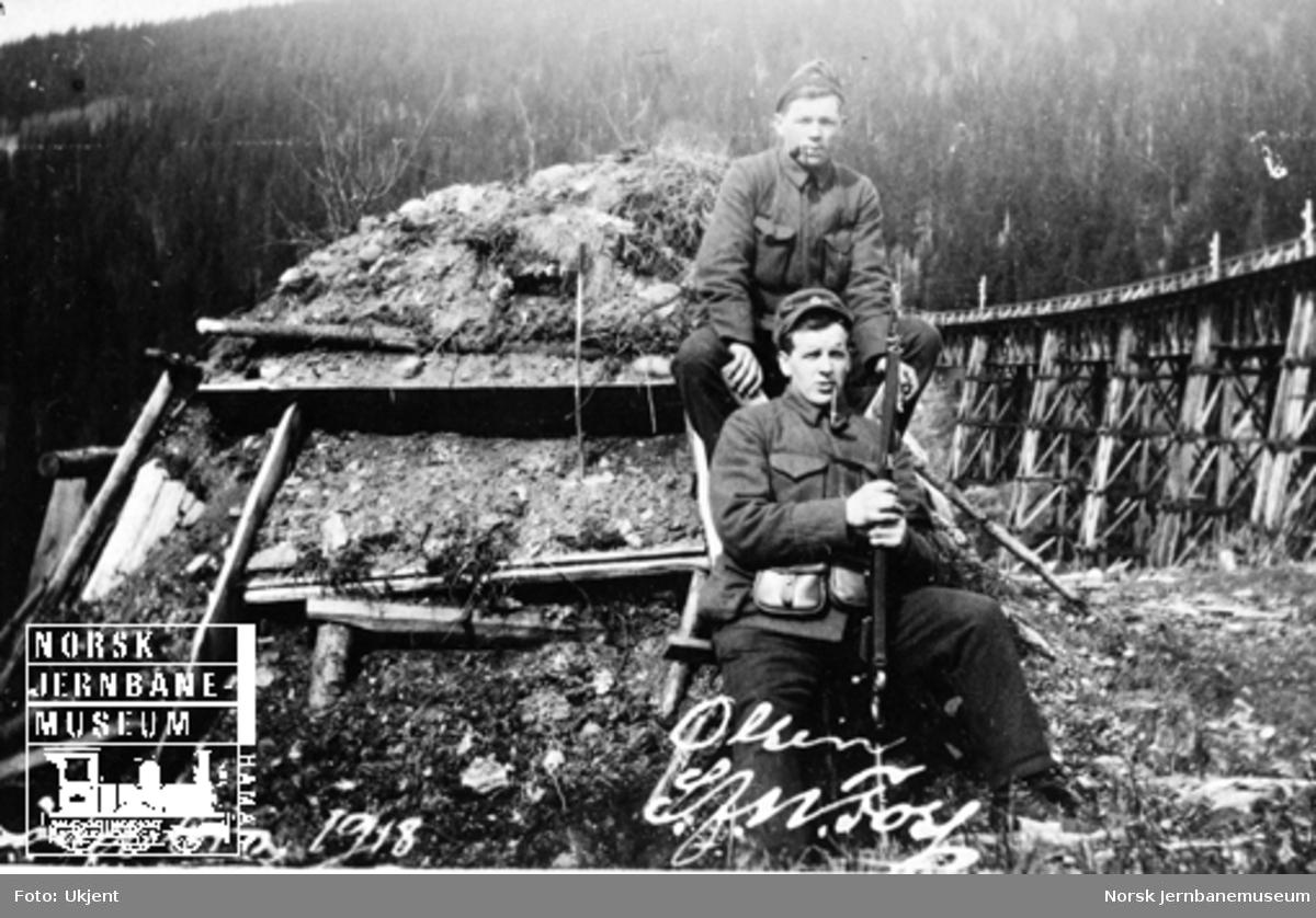 To militære foran ei torvhytte med Drøia bru i bakgrunnen