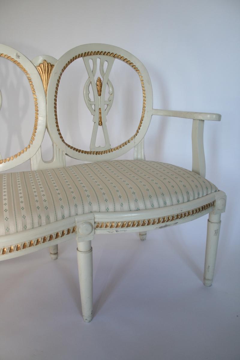 Hvitmalt med forgylt dekor. Ryggen er firdelt, ovaler. Louis Seize-stil