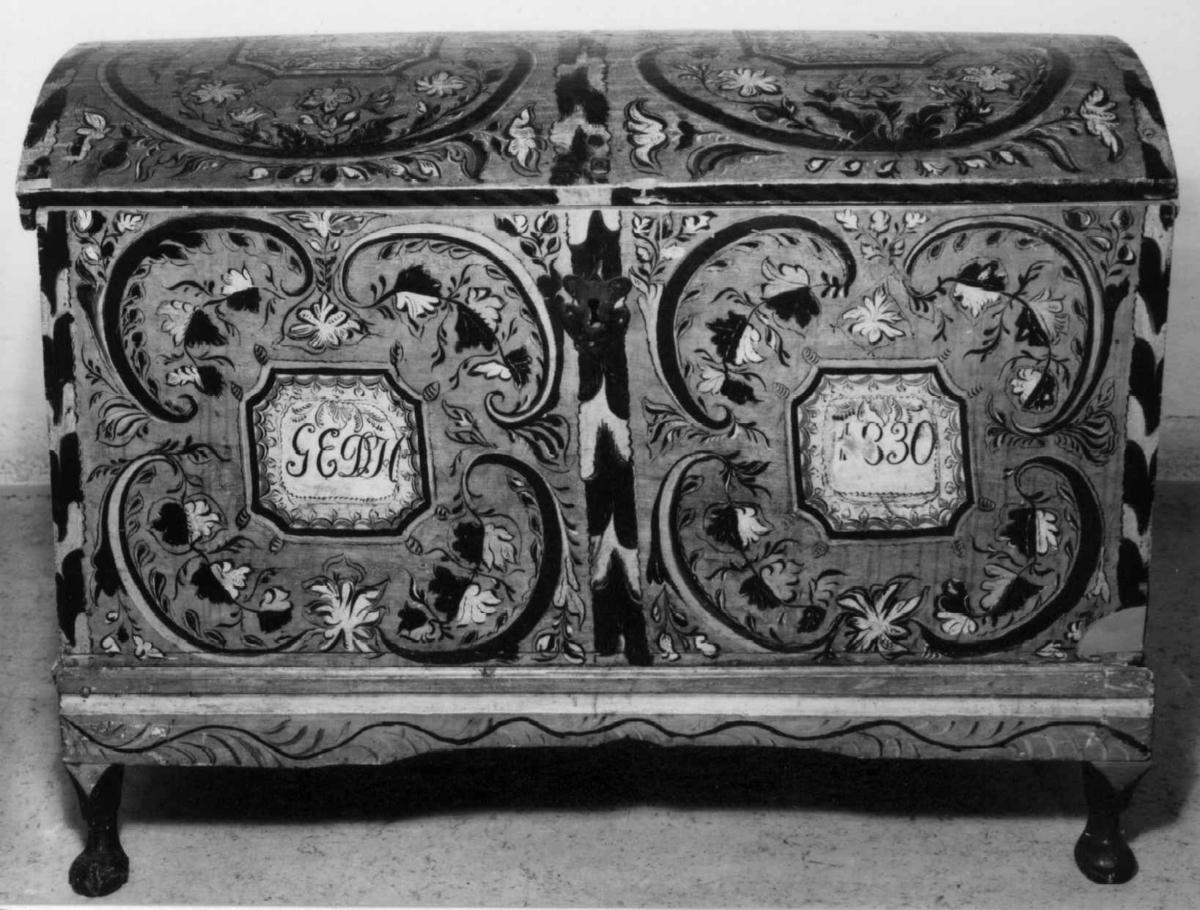 Kiste med svakt buet lokk og rosemalt dekor. Kisten har hatt tilhørende sokkel.