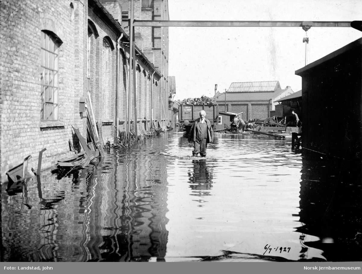 Flommen i 1927 : NSBs verksted Hamar, vannstand 8,10 meter, med fotografen, inspektør Landstad. Smie og maskinverksted til venstre